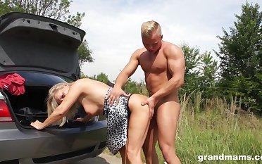 Tanned of age wrinkled whore flashes tits as she is fucked hard not far from the car