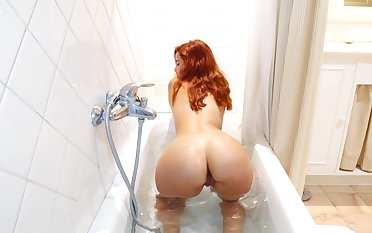 Libidinous red head Agatha is playing here her favorite sex toy in the shower